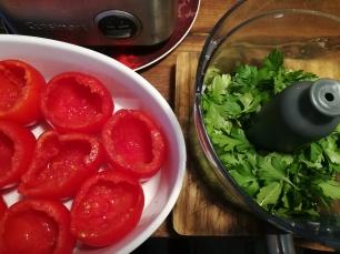 Vue sur des tomates vidées et placée dans un grand plat à gratin et sur un robot cuisiner rempli de persil prêt à être ciselée - Tomates farcies - BouffePorn
